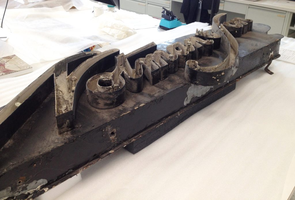 Fig. 1. The Notman & Son neon sign in the conservation lab before treatment, showing large amounts of surface dirt and paint losses. The neon glass tubing is also missing.